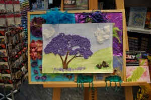 Gorgeous Tactile Artwork, created by Jill Huber, and mounted on a background of arrangements from the Tactile art workshop. This piece is installed at Eckersleys Art shop in Westfield Penrith.