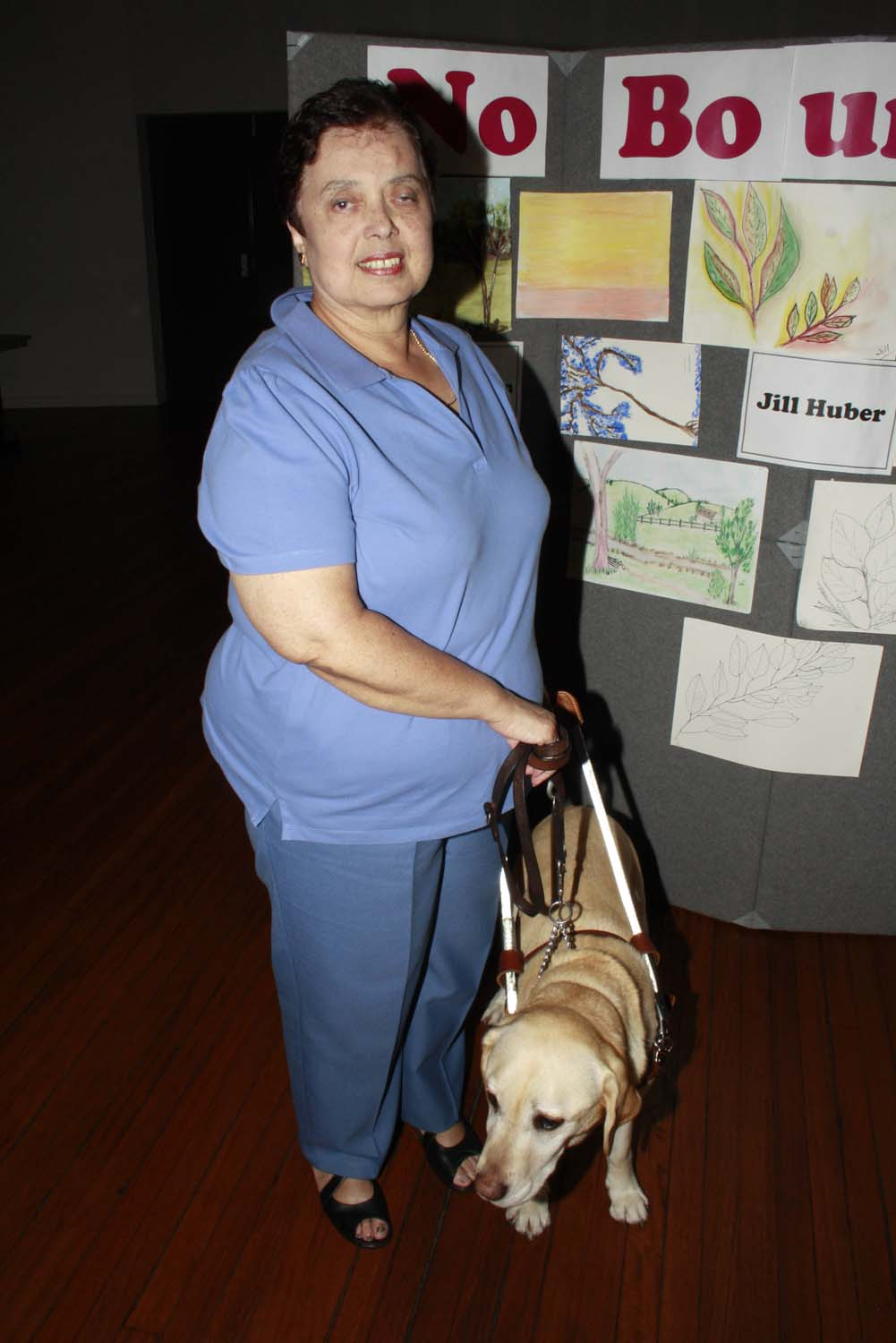 Jill Huber with her artwork and guide dog